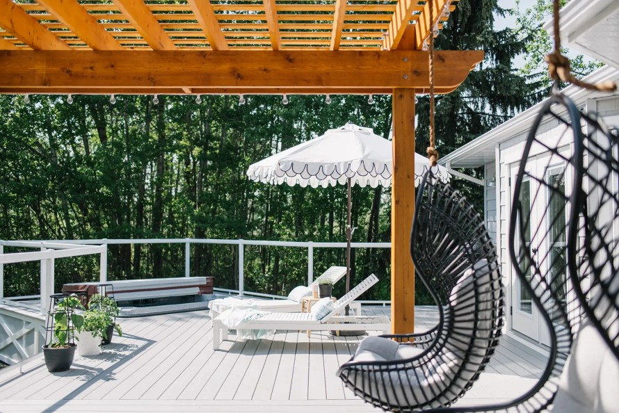 Grey deck with loungers and hanging chairs.