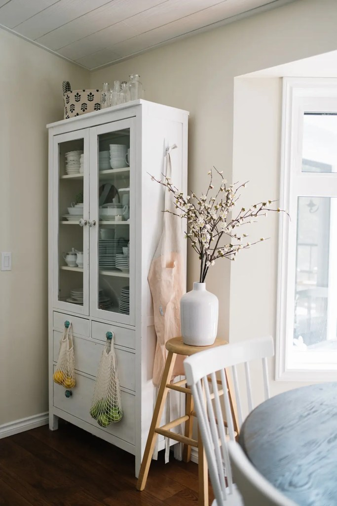 faux cherry blossoms in large vase on wooden stool