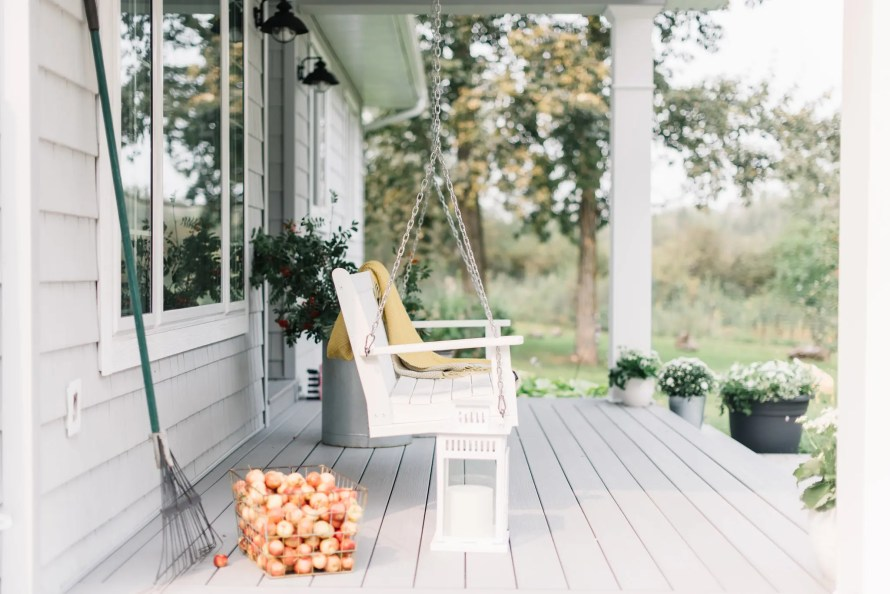 A simple fall porch decorated with apples, cut branches and a few flowers.
