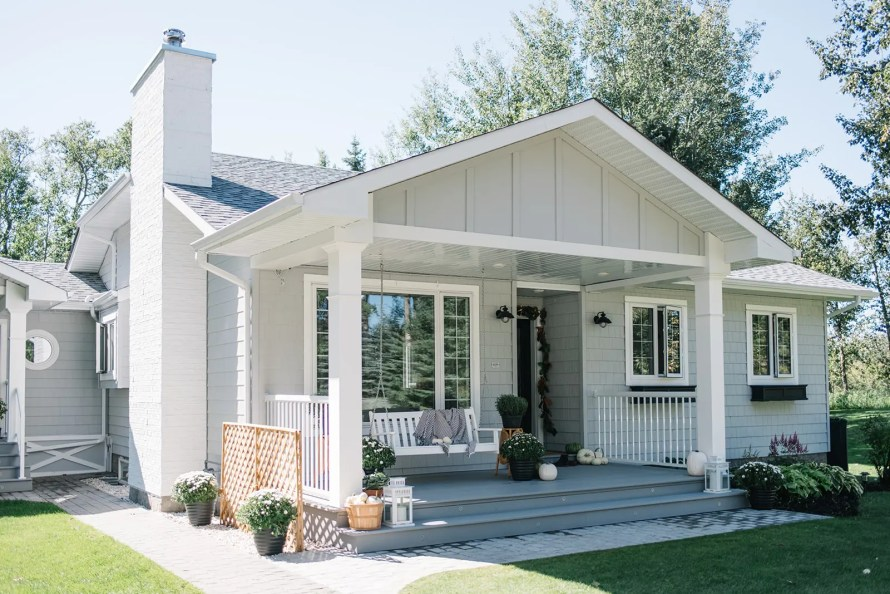 Modern Country cottage farmhouse style home with grey siding and a white chimney