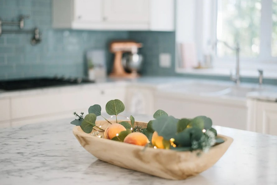 A doughbowl looks pretty filled with eucalyptus, twinkle lights and peaches