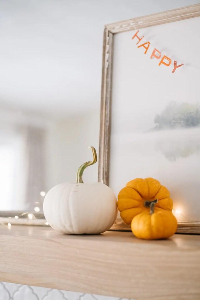 white and orange mini pumpkins and twinkle lights