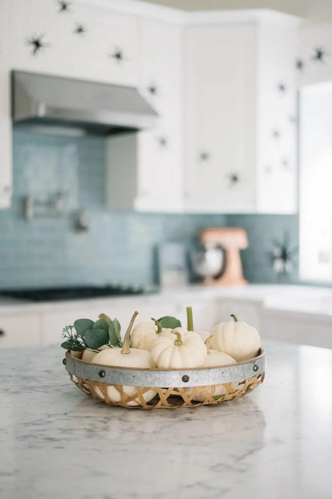 basket of tiny white pumpkins on kitchen island