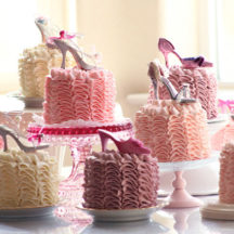 pink ruffle cakes on various plates and cake stands on a table. Cakes each have miniature shoe decoration on top