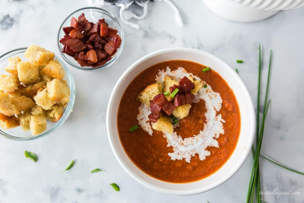 overhead view of tomato bisque in white bowl; croutons, bacon, and chives on top of the soup and also in bowls to the side