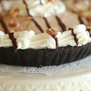 mud pie with whipped cream border and chocolate drizzle/toasted almonds on top, sitting on doily and cream cake stand
