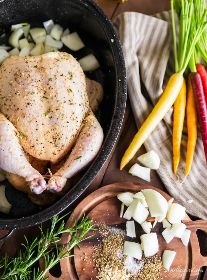 whole roasted chicken in black roasting pan with rainbow carrots, chopped white onion, and fresh herbs on a striped tea towel