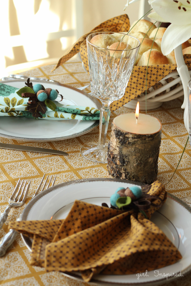 Table setting with gold and blue linens, a burning candle, and crafted felt blue acorns