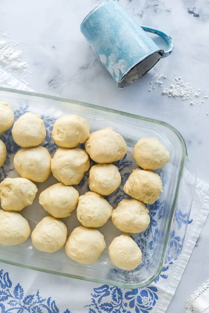 overhead view of raw dinner roll dough balls in clear glass baking dish with blue floral linen below and blue cup with flour