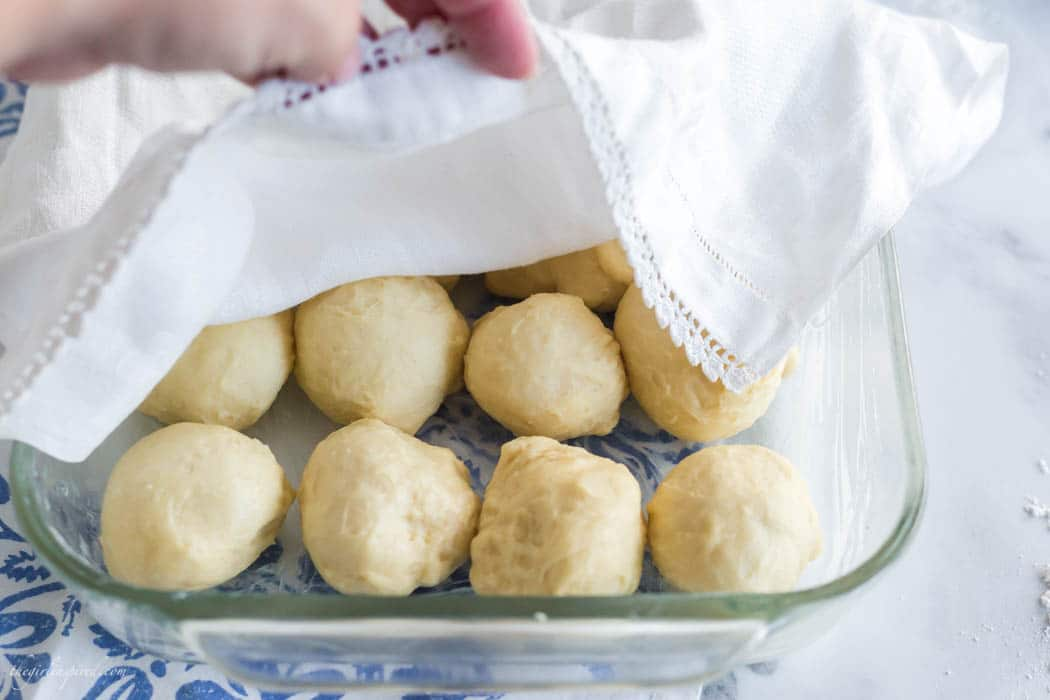 raw dinner roll dough balls in clear glass baking dish with blue floral linen below and white dish towel over the top