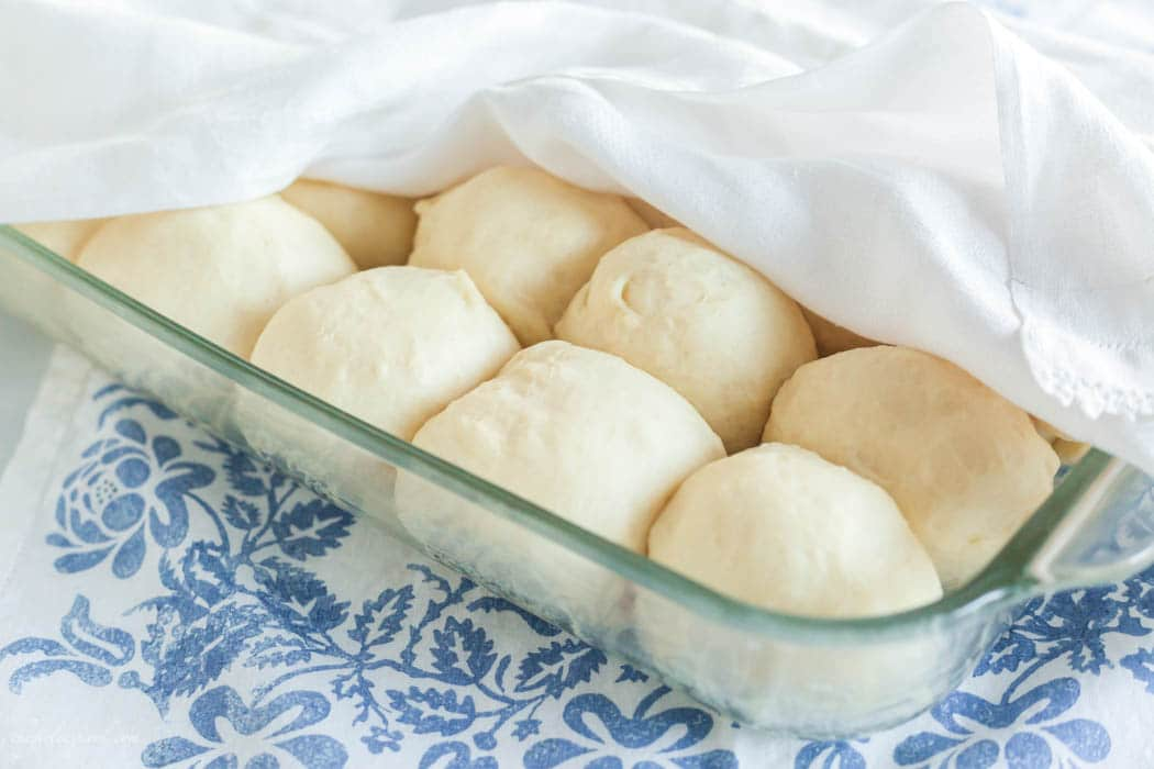 uncooked, risen dinner rolls in clear glass baking dish with blue floral linen below and white dish towel over the top