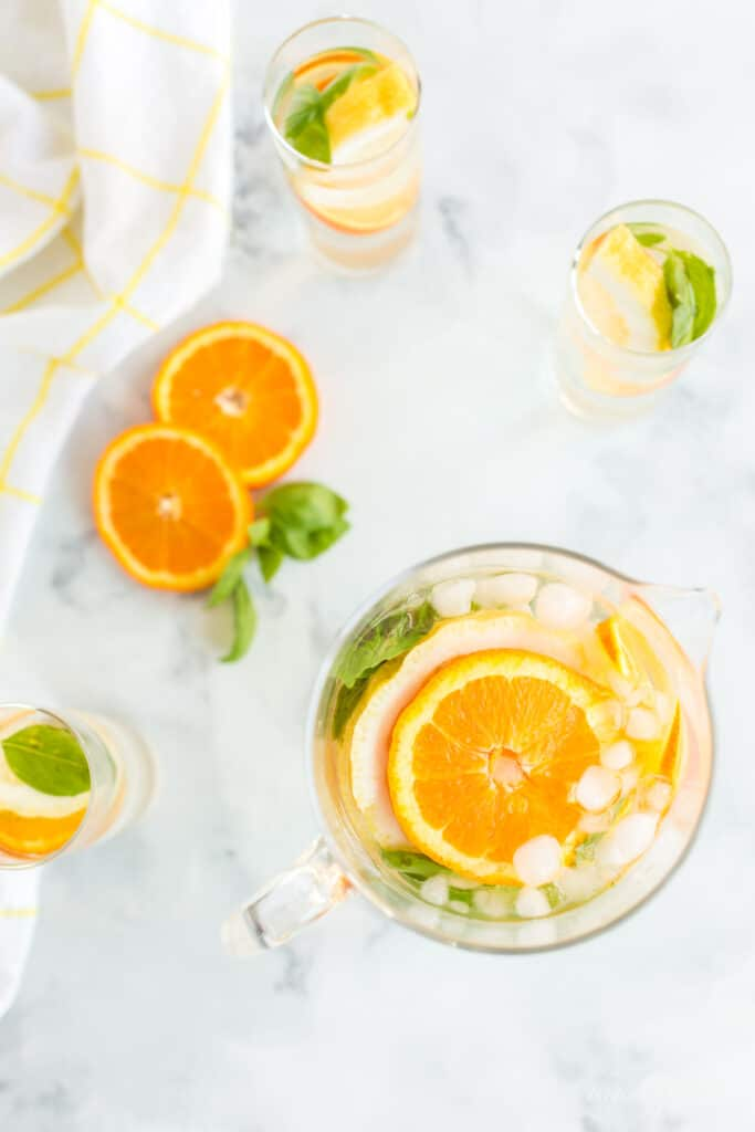 orange slices, lemon slices, and basil leaves with ice and water in glass pitcher and water glasses