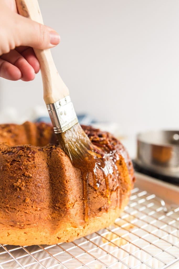pastry brush drizzling glaze onto top and side of Bacardi rum cake