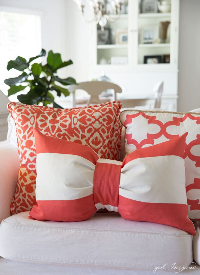 Coral and white bow pillow and coral and white square pillows on white couch