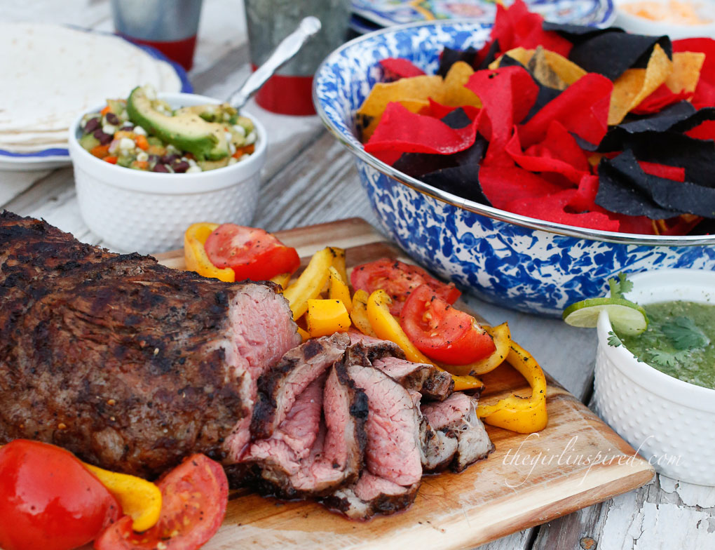 grilled and sliced tri tip on wooden cutting board with veggies, paper plates and utensils, bowl of red and blue tortilla chips