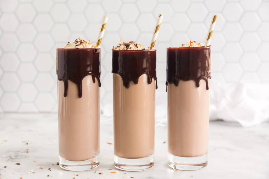 three tall glasses with chocolate dripping from rim, filled with chocolate milk and liquor and topped with whipped cream and gold stripes straws