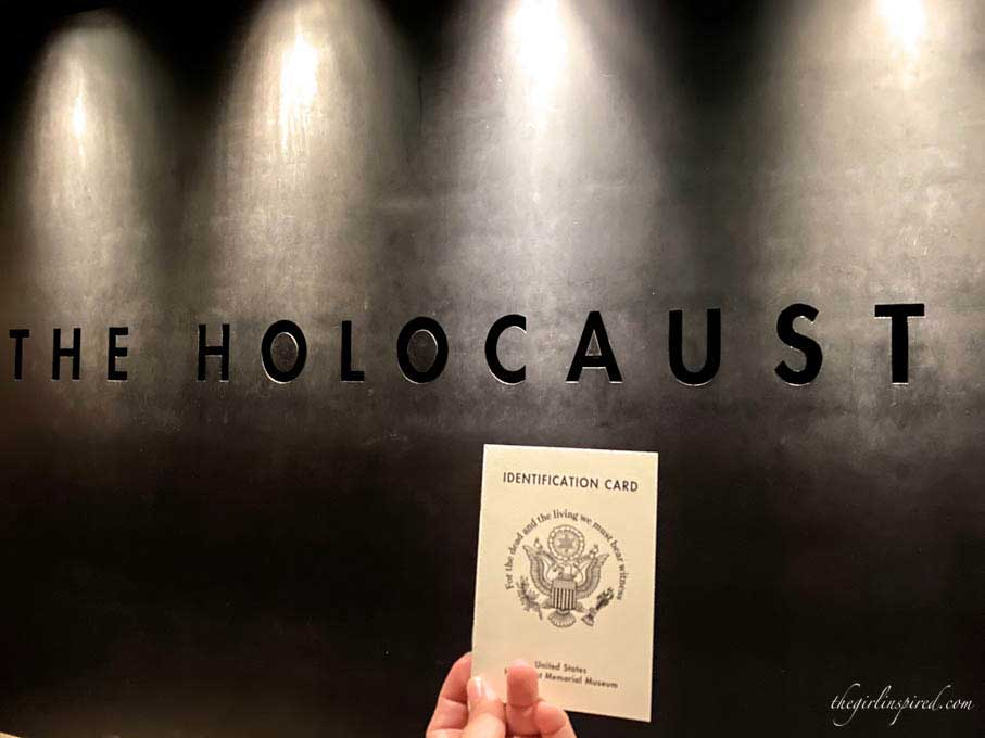 """Small white booklet held in front of wall engraved """"Holocaust"""""""