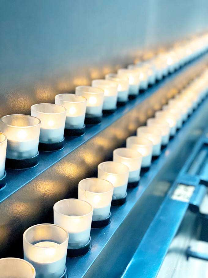 rows of lit tea light candles