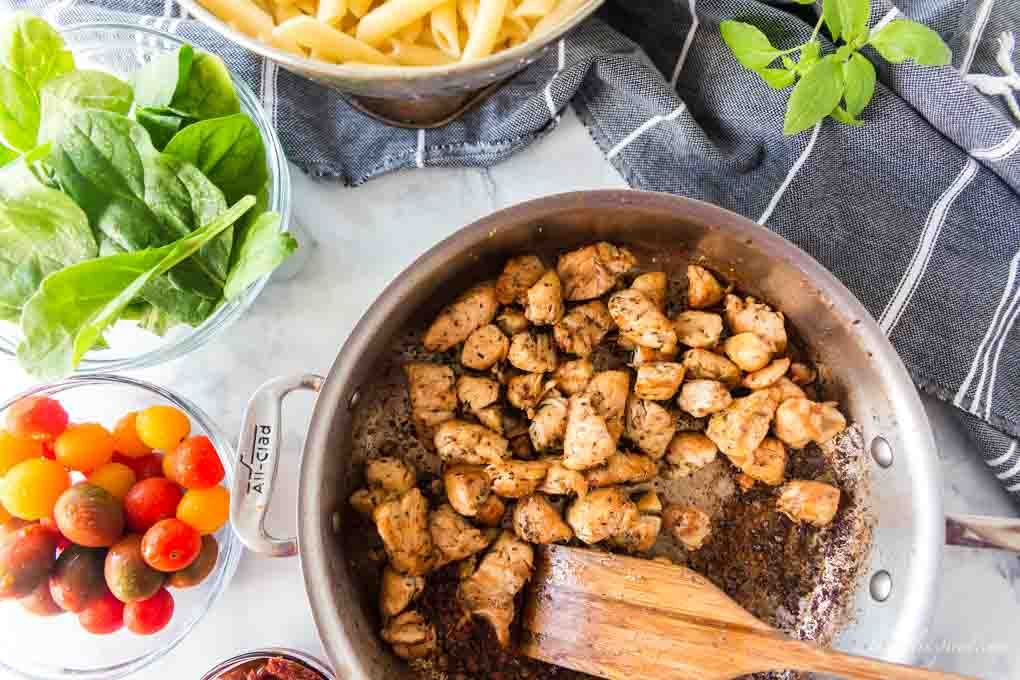 browned chicken in saucepan with dishes of tomatoes, spinach and cooked pasta in background