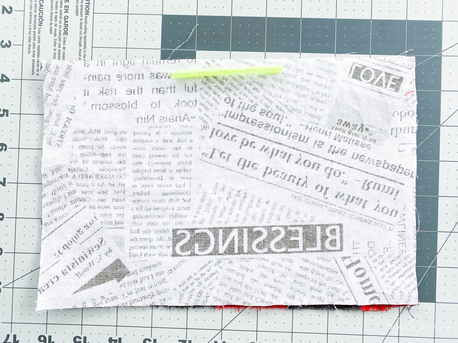 newsprint patterned fabric with neon yellow pipe cleaner on a rulered mat