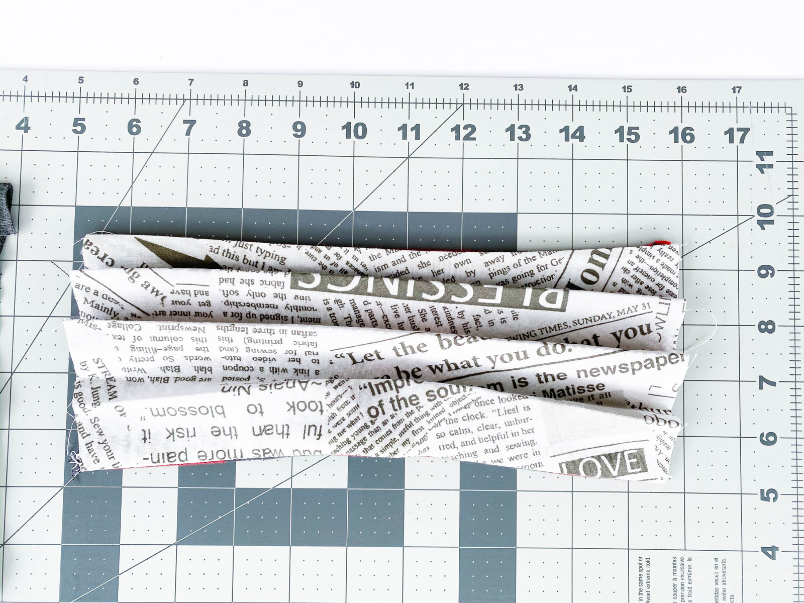 pleated folds in newsprint fabric mask on rulered mat