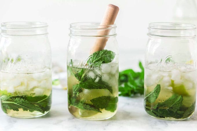 three mojitos in mason jars garnished with lime, mint, and bamboo straws