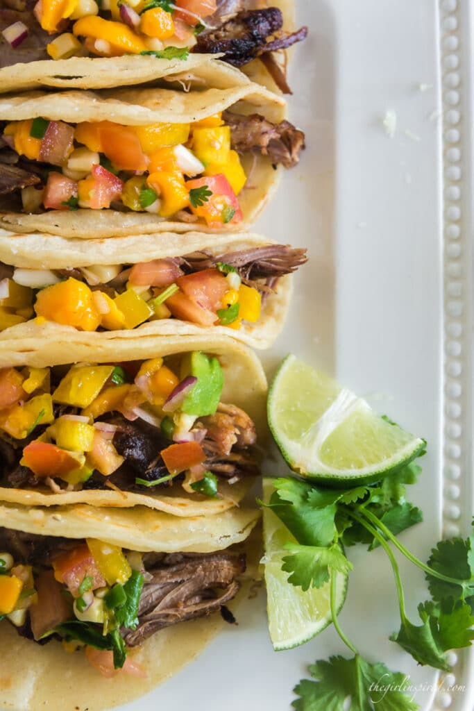 overhead photo of tacos lined up on white plate with mango avocado salsa garnish and lime and cilantro garnish