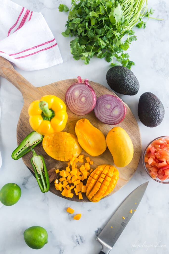 overhead photo of fruits and vegetables whole or partially chopped on a cutting board with knife and red and white linen