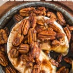 browned pecans and brown sugar over brie in a baking dish on a wooden serving board with text overlay