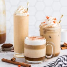 three different sized glasses with pumpkin spice lattes; hot, on ice, and blended, with whipped cream