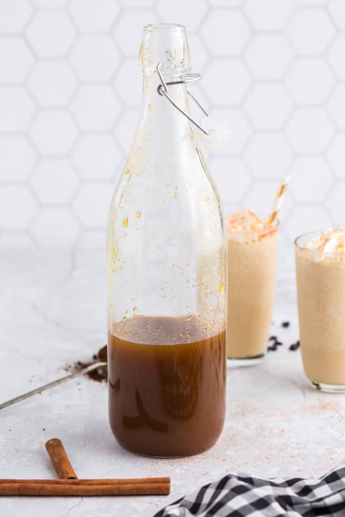 bottle of pumpkin spice syrup with lattes in the background