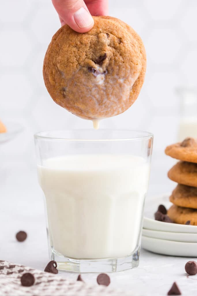 cookie dunked into glass of milk with stack of cookies in the background