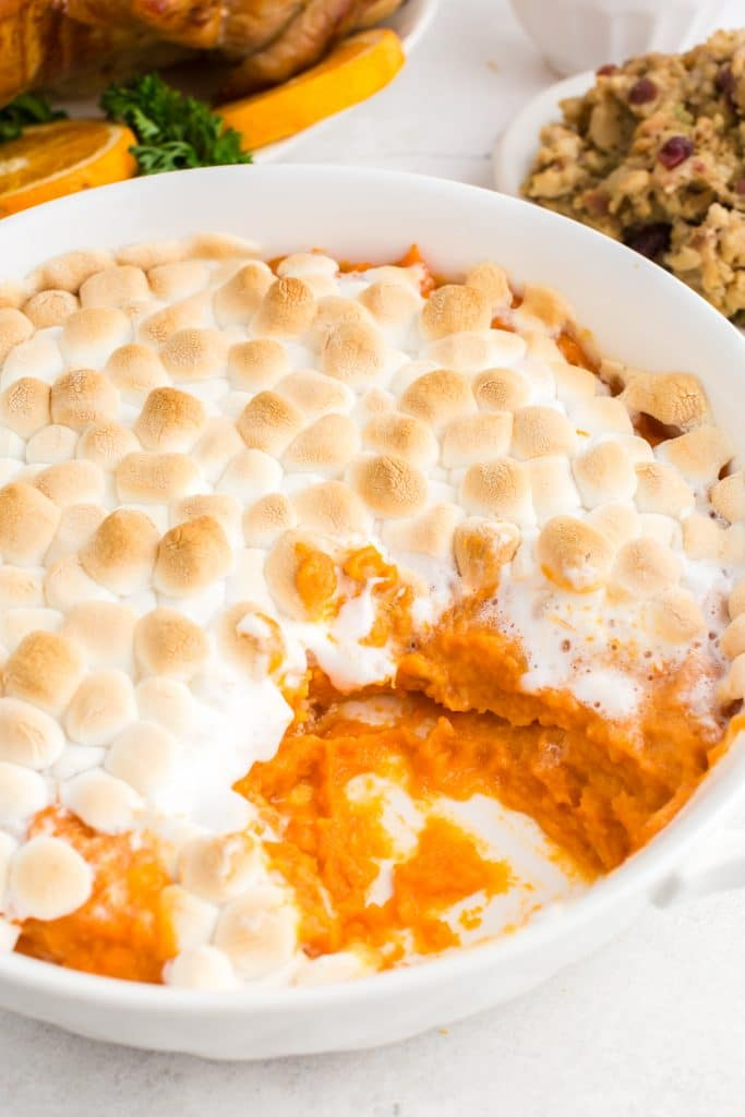 closeup of candied yams with toasted marshmallows in white dish with scoop removed