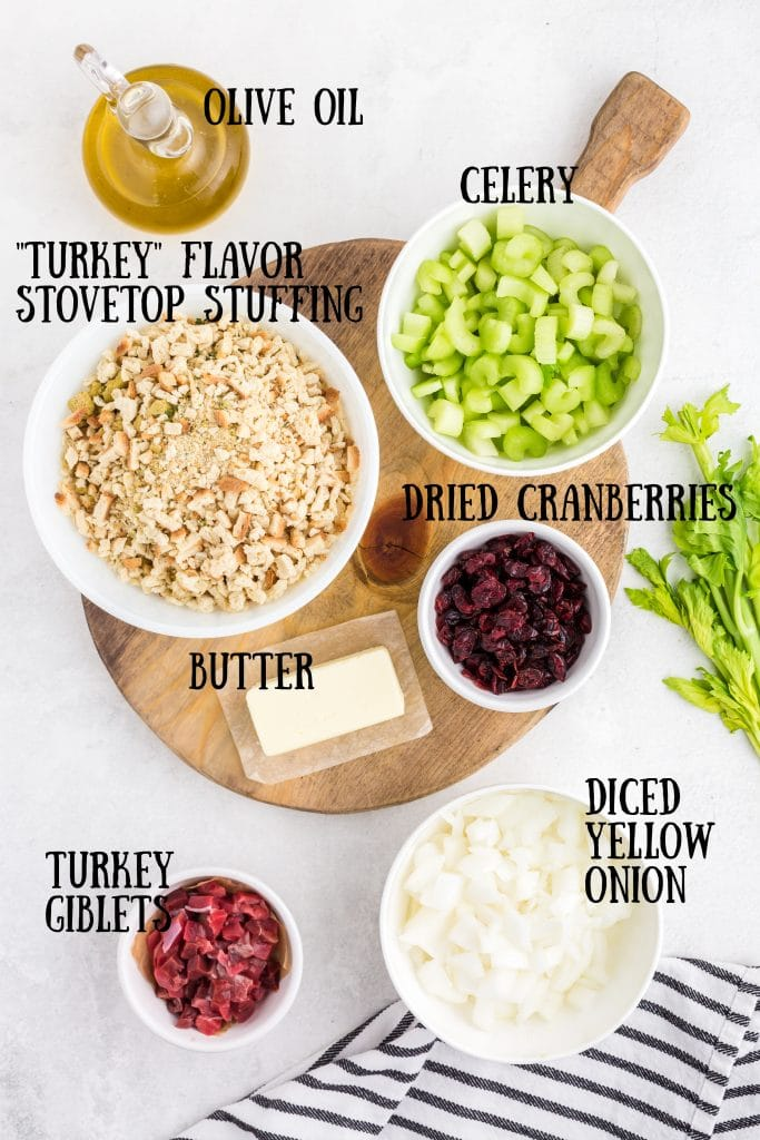 overhead photo of ingredients for Thanksgiving stuffing - olive oil, diced celery and diced onions in white bowls, bread crumbs in white bowl, stick of butter, bowls of dried cranberries and giblets, celery stalks and black and white striped towel
