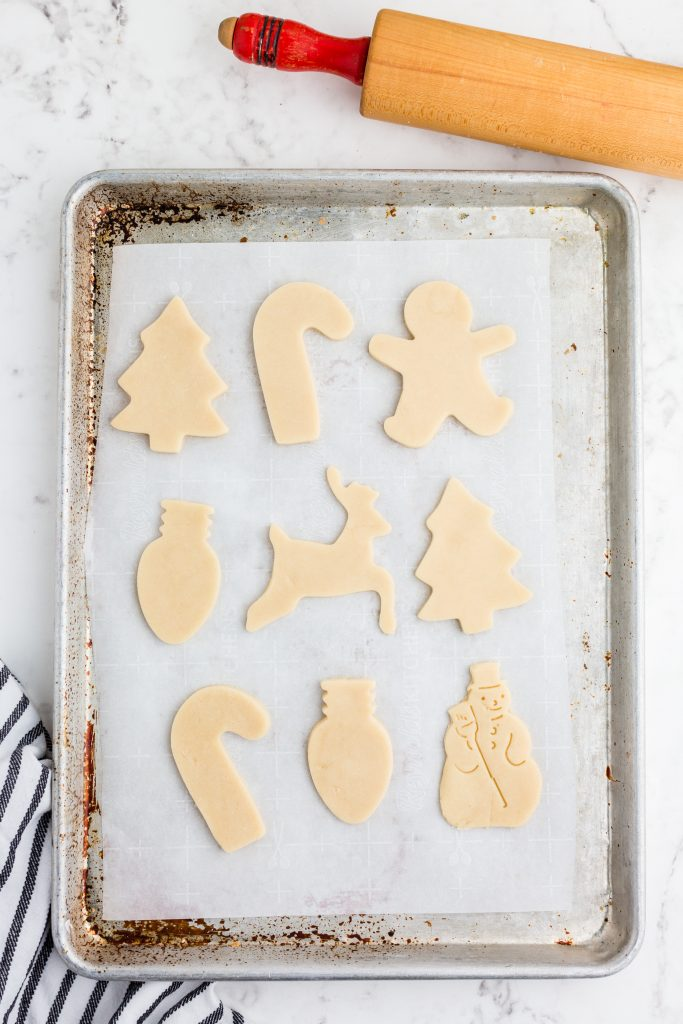 Christmas cut out cookies ready to be baked on cookie sheet