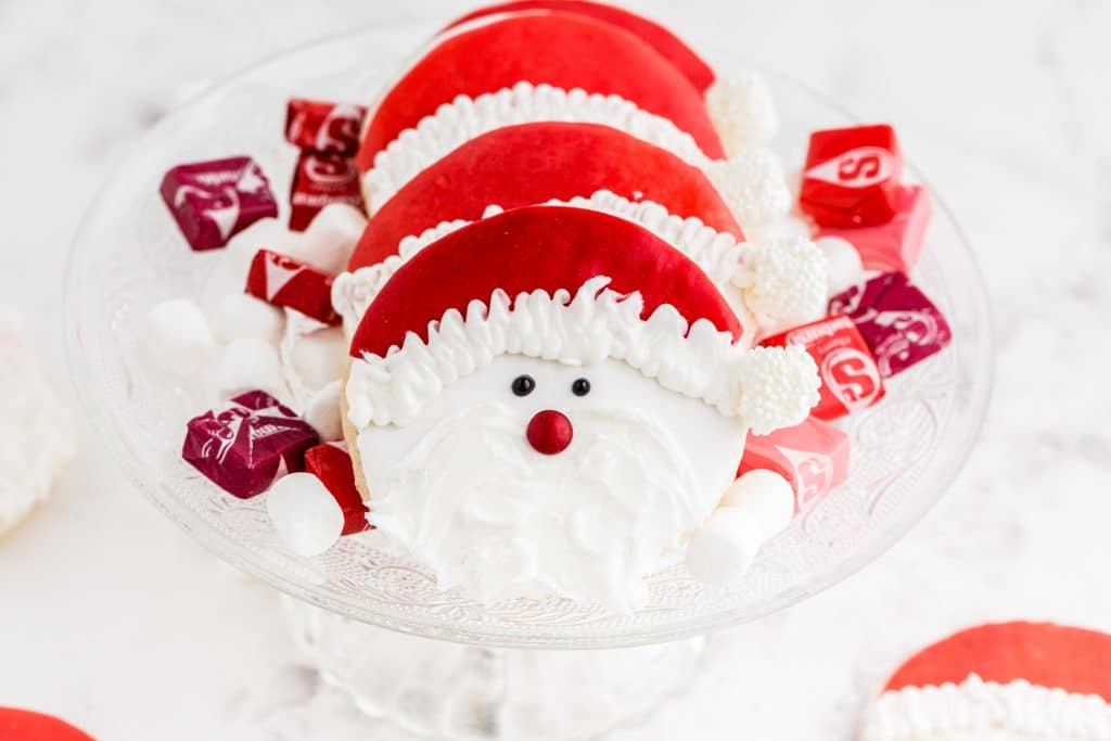 santa cookies on glass cake stand with starburst and marshmallows scattered around