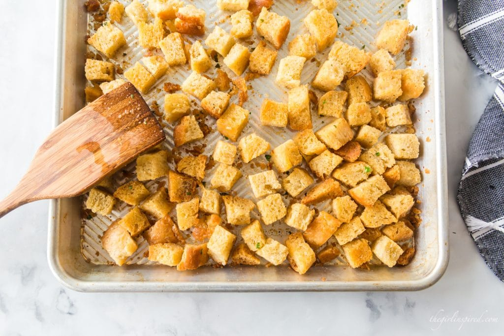homemade croutons browned and spread out on baking sheet with wooden spatula
