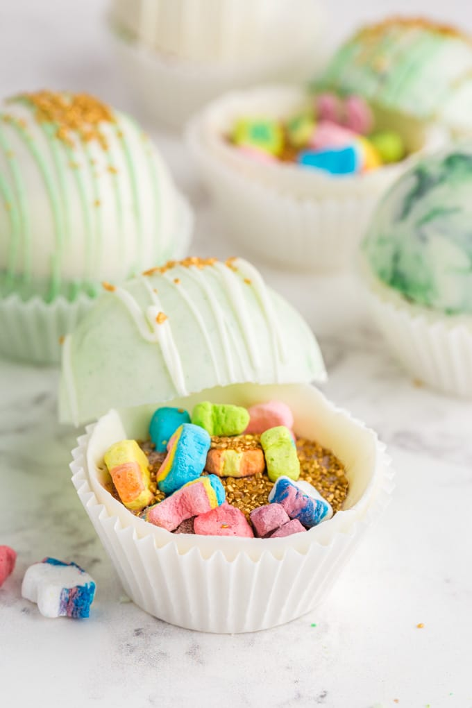 White and green marbled hot chocolate bombs propped open with gold sprinkles and Lucky Charms marshmallows inside