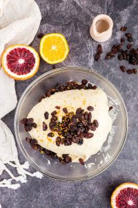 raisins and orange peel mounded on top of dough in glass bowl, oranges and raisins in periphery