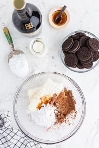 chocolate cheesecake ingredients in glass mixing bowl with other trifle ingredients like oreos and Bailey's set nearby