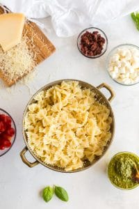 bowtie pasta in colander with pesto, cheese, and tomatoes in nearby bowls