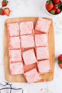 overhead of strawberry brownies cut into squares on cutting board
