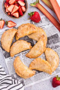 Batch of backed Strawberry Rhubarb Hand Pies on newspaper