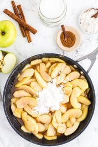 Frying pan with apple mixture and flour, bowl with ground cinnamon, cinnamon sticks, bowl with flour, an apple on marble countertop