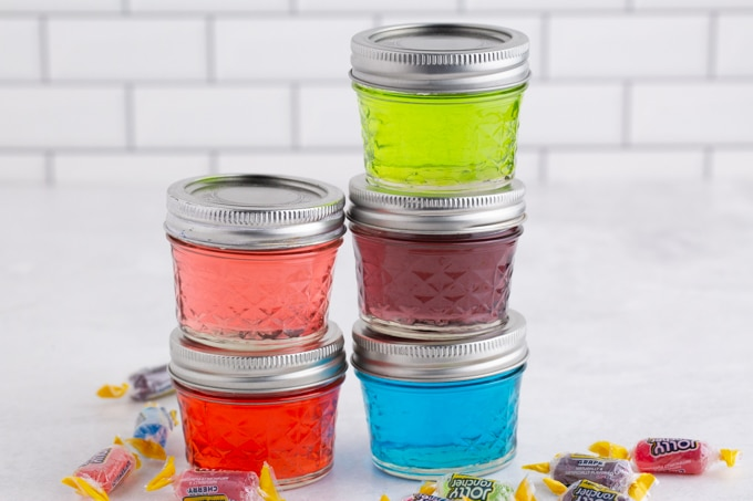 Five glasses with lid filled with different colored Jolly Rancher Candy dissolved in vodka, jolly rancher candy, white subway tiles in the background