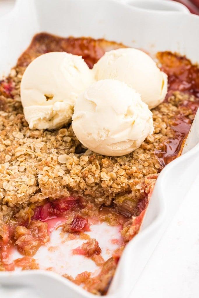 baked Rhubarb Crisp in white pie dish, three scoops of vanilla ice cream on top