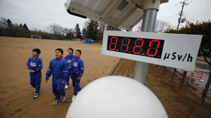 Students walk near a geiger counter, measuring a radiation level of 0.12 microsievert per hour, at Omika Elementary School, located about 21 km (13 miles) from the tsunami-crippled Fukushima Daiichi nuclear power plant, in Minamisoma, Fukushima prefecture.(Reuters / Toru Hanai)