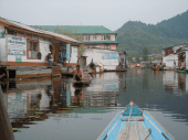 Shikara glides past shops on the Dal Lake