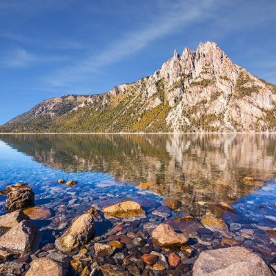 Picturesque mountain in San Carlos de Bariloche, Argentina. The mirror water of lake reflects sharp rocks. The concept of exotic and extreme tourism
