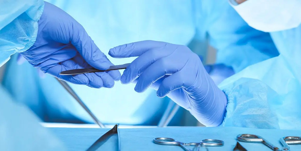 Surgeon passing medical instrument wearing blue gloves